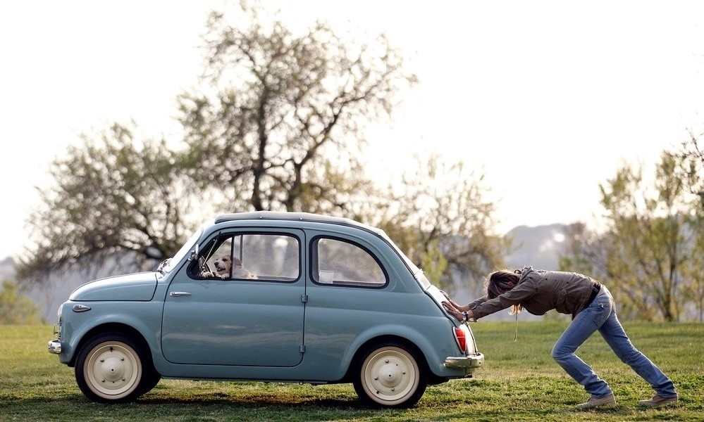 File photo of woman pushing her Fiat 500 car as her dog sits inside, in neighbourhood of Rome